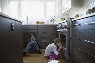 Girl peering into oven in kitchen - HEROF35303