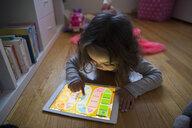 Girl playing game on digital tablet on floor - HEROF35312