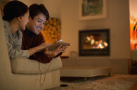 Happy couple with headphones sharing digital tablet on living room sofa - HOXF04408