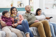 Family watching TV on living room sofa - CAIF23143
