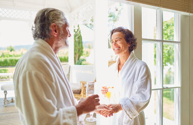 Happy mature couple in bathrobes drinking mimosas at hotel balcony doorway - CAIF23152