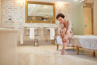 Woman putting on high heel sandals in luxury hotel bathroom - CAIF23158
