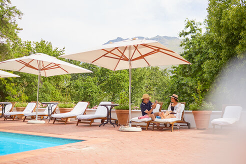 Mature couple relaxing on lounge chairs at resort poolside - CAIF23167