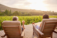 Couple relaxing, drinking wine on sunny, idyllic resort patio - CAIF23170