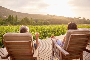 Couple relaxing, drinking wine on sunny, idyllic resort patio - CAIF23170