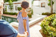 Couple holding hands, walking at sunny poolside - CAIF23182
