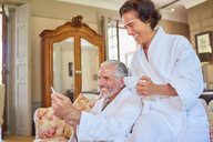 Happy mature couple in spa bathrobes drinking coffee in hotel room - CAIF23191