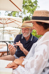 Happy mature couple using smart phone at resort poolside - CAIF23194