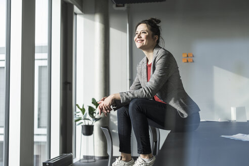 Businesswoman sitting on desk in office looking out of window - UUF17087