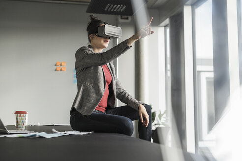 Businesswoman sitting on desk in office wearing VR glasses - UUF17090