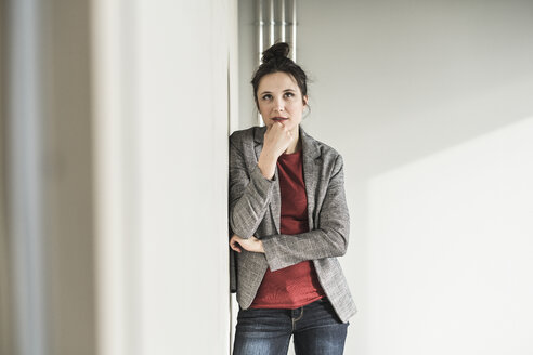 Portrait of businesswoman leaning against a wall in office thinking - UUF17099