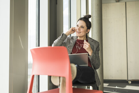 Smiling businesswoman sitting on chair in office with laptop and earphones - UUF17102