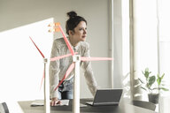 Businesswoman with wind turbine models and laptop on desk in office - UUF17108