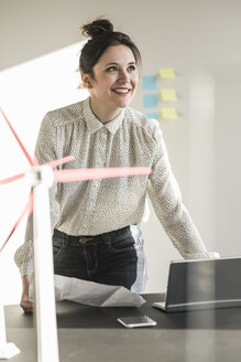 Smiling businesswoman with wind turbine model and laptop on desk in office - UUF17111