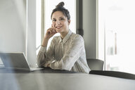 Portrait of smiling businesswoman with laptop sitting at desk in office - UUF17114