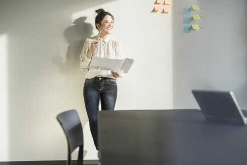 Smiling businesswoman holding plan in office - UUF17117