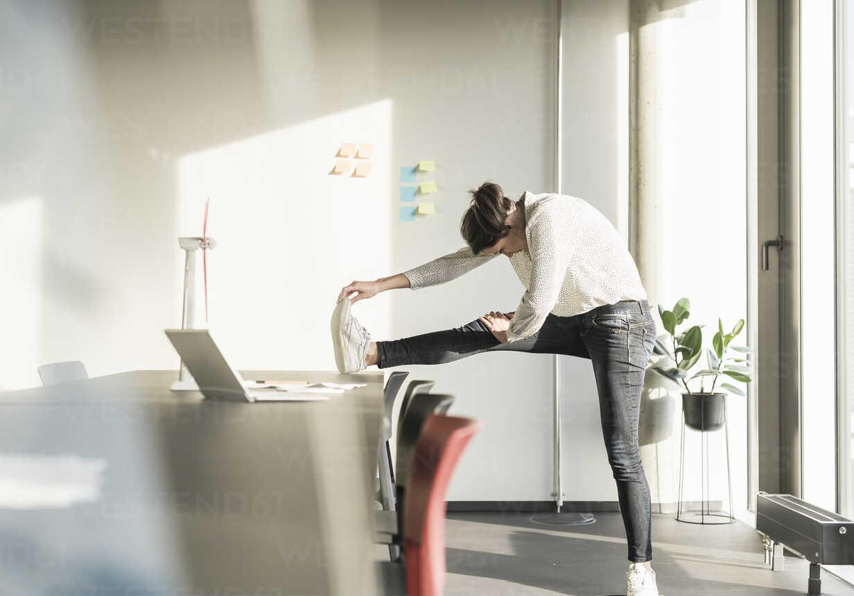 Businesswoman stretching in office - UUF17120 - Uwe Umstätter/Westend61