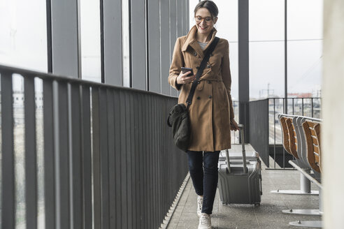 Smiling businesswoman walking with baggage and cell phone - UUF17132