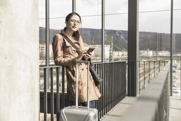 Portrait of businesswoman with baggage and cell phone - UUF17135