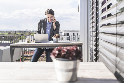 Smiling businesswoman with cell phone and laptop on roof terrace - UUF17141