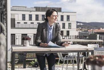 Smiling businesswoman using cell phone on roof terrace - UUF17144