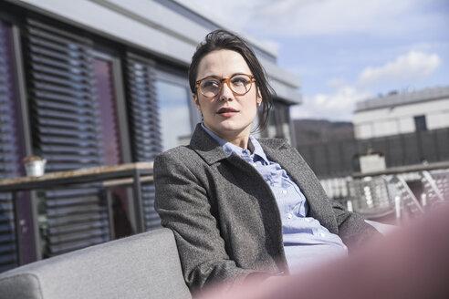 Businesswoman sitting on roof terrace looking around - UUF17150
