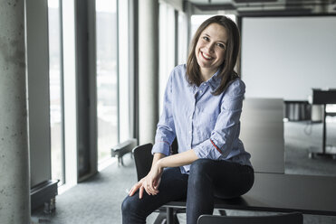 Portrait of smiling businesswoman sitting on conference table in office - UUF17153