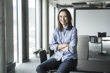 Portrait of smiling businesswoman sitting on conference table in office - UUF17156