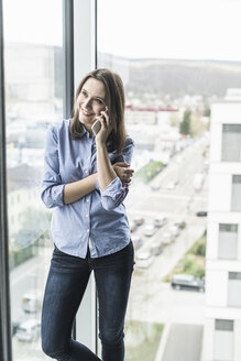 Smiling businesswoman on cell phone standing at the window in office - UUF17159