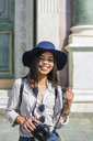 Italy, Florence, portrait of happy young tourist with camera and sunglasses - MGIF00333