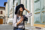 Italy, Florence, happy young tourist with camera looking up - MGIF00336