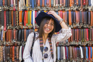 Italy, Florence, portrait of laughing young tourist on street market - MGIF00339