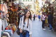 Italy, Florence, portrait of happy young tourist with camera exploring street market - MGIF00342