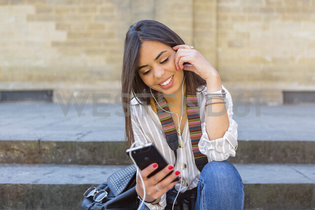 Italy, Florence, portrait of young tourist sitting on stairs listening music with earphones and smartphone - MGIF00345 - Giorgio Magini/Westend61