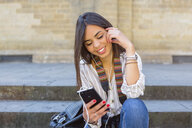 Italy, Florence, portrait of young tourist sitting on stairs listening music with earphones and smartphone - MGIF00345