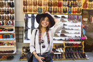 Italy, Florence, portrait of happy young tourist with camera and backpack on street market - MGIF00348