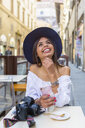 Italy, Florence, portrait of happy young tourist drinking espresso at pavement cafe - MGIF00357