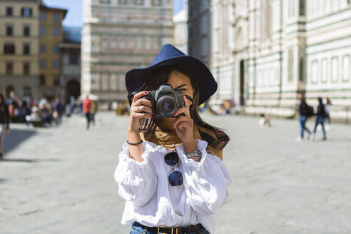 Italy, Florence, Piazza del Duomo, young tourist taking photo with camera - MGIF00366