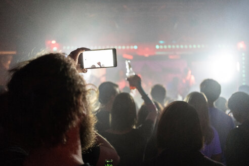 Man taking photograph of concert with smartphone - CUF49952