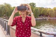Young woman using VR headset on bridge, river in background, Berlin, Germany - CUF49955