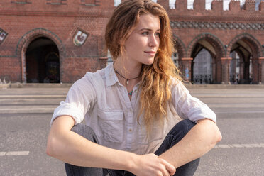 Young woman resting on Oberbaum bridge in city, Berlin, Germany - CUF49958