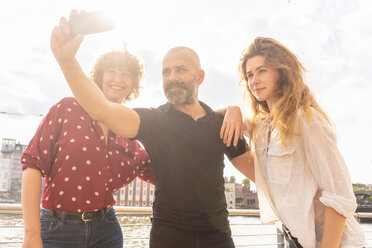 Man and female friends taking selfie with smartphone on bridge - CUF49961