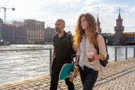 Man and female friend with skateboard on bridge, river, Oberbaum bridge and buildings in background, Berlin, Germany - CUF49964