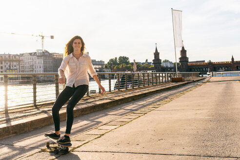 Young woman skateboarding on bridge, river and buildings in background, Berlin, Germany - CUF49970