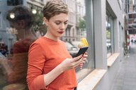 Woman holding ice cream and using smartphone in front of shop, Cologne, Nordrhein-Westfalen, Germany - CUF49991