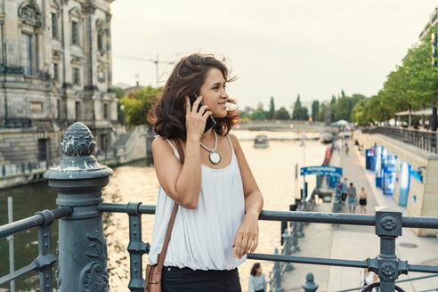 Female student using smartphone by river, Berlin, Germany - CUF50018