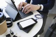 Businessman traveling, using laptop at cafe table - HEROF35416