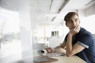 Thoughtful businessman with digital tablet looking over shoulder - HEROF35452