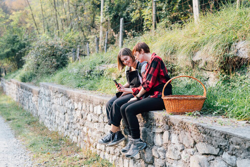 Best friends sitting on stone wall, sharing text message, Rezzago, Lombardy, Italy - CUF50095