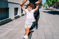 Father teaches son skateboarding on sidewalk - CUF50098